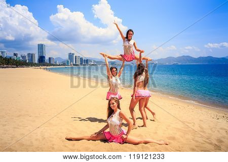 Cheerleaders Perform High Straddle Stunt On Beach Against Sea