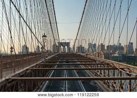 Deserted Traffic Lanes and Support Beams and Cables of Historic Brooklyn Bridge Crossing East River and Looking Towards Borough of Brooklyn, New York City, New York, USA at Sunrise