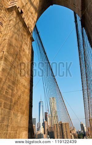 Low Angle View of One World Trade Center Skyscraper Amongst Manhattan Buildings as seen through Arch on Brooklyn Bridge, New York City, New York, USA