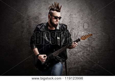 Young punk rocker playing electric guitar and leaning against a concrete wall