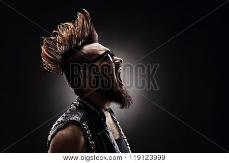Profile shot of an angry punk rocker shouting on dark background