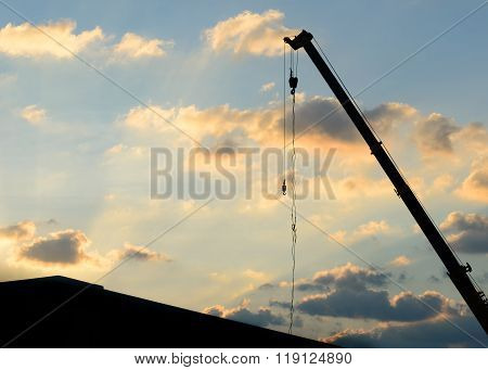 mobile crane operating silhouettes at sunset background