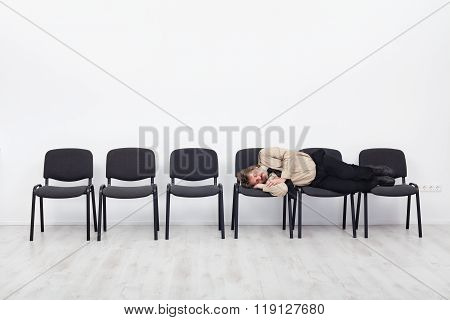 Office Worker Asleep On Row Of Chairs
