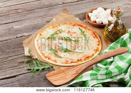 Quattro fromaggi pizza with lettuce on wooden table