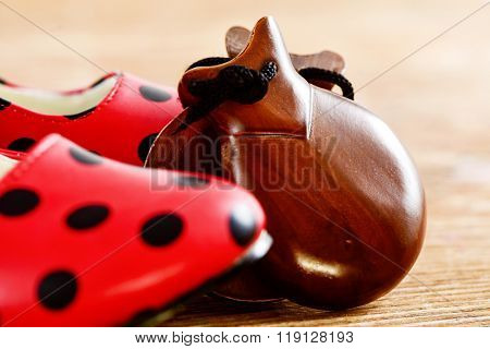 closeup of a pair of castanets and a pair of typical dot-patterned red flamenco shoes, on a wooden surface