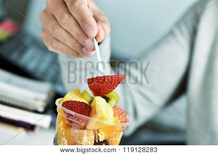 closeup of a young caucasian man eating a fruit salad from a clear plastic cup at the office