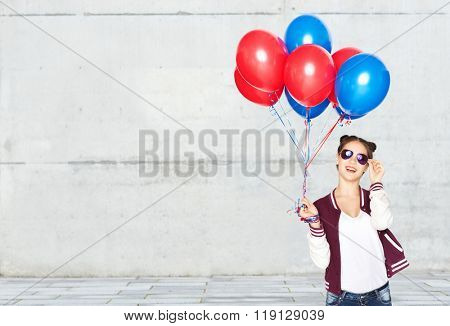 people, teens, holidays, party and summer concept - happy smiling pretty teenage girl in sunglasses with helium balloons over gray stone wall background