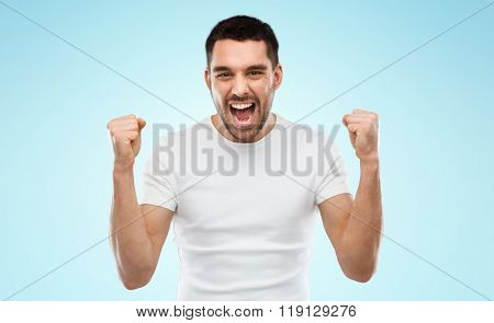 emotion, success, gesture and people concept - young man celebrating victory over blue background