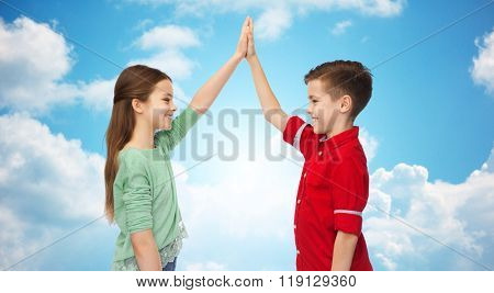 childhood, friendship, gesture and people concept - happy smiling boy and girl making high five over blue sky and clouds background