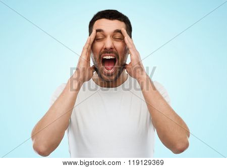 emotions, stress, madness and people concept - crazy shouting man in t-shirt over blue background