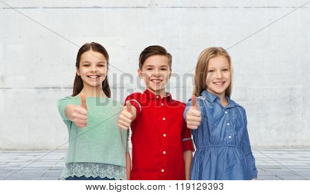 childhood, friendship, gesture and people concept - happy smiling children showing thumbs up over urban street background