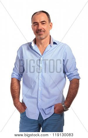 confident mature bald man posing smiling with hands in pockets while looking at the camera in white isolated studio background