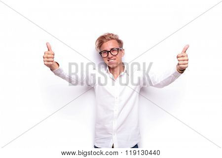 young confident blonde man showing thumbs up with open arms while smiling a nd looking away from the camera in white isolated studio background