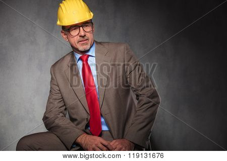 elegant senior engineer wearing helmet and glasses while posing seated looking away in studio  background