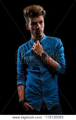 portrait of fashionable boy wearing denim posing in dark studio background with hand in pocket while fixing his shirt and looking away from the camera