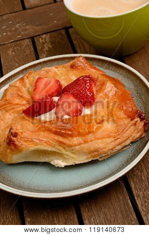 Danish pastry with fresh strawberries on a wooden garden table