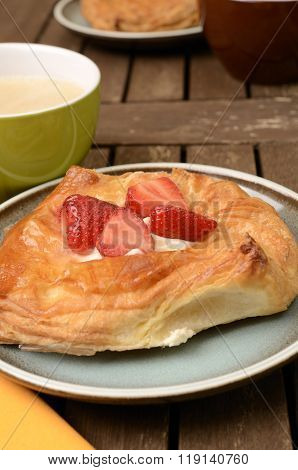 Sweet danish pastry with fresh strawberries on a plate