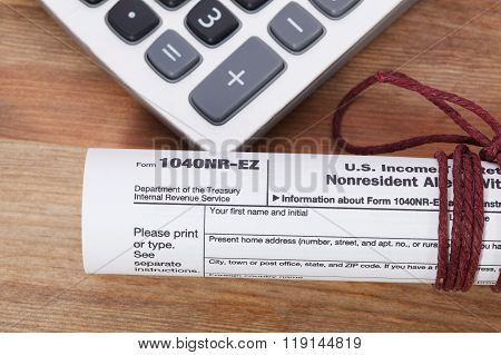 Tax Form And Calculator On Wooden Table