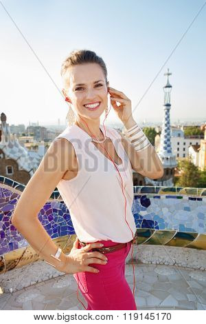 Smiling Woman Listening Audioguide In Park Guell, Barcelona