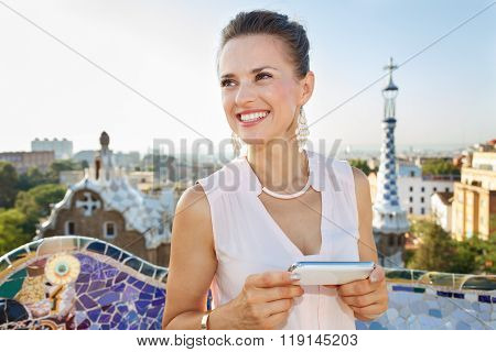 Woman With Smartphone Looking Into Distance In Park Guell, Spain