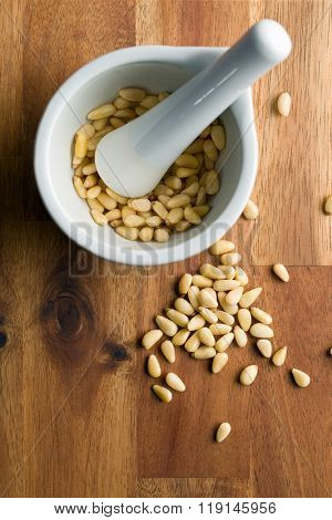 pine nuts in ceramic mortar
