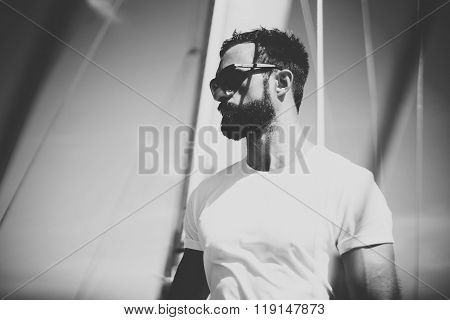 Portrait of young bearded man standing on the yacht in sunny day. Horizontal