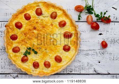 Open Pie Quiche Lauren With A Chicken On A White Wooden Table