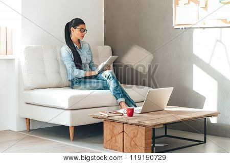 Great working day. Beautiful young woman in glasses working with touchpad while sitting on the couch in office