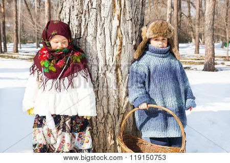 Children In Russian Scarf On Head With Floral Print And With  Bunch Of Bagels On Background Of Snow.