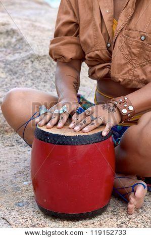 Girl's hands on bright drum, rings, mehendi, ethnic photoshooting.