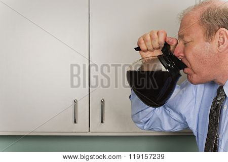 Businessman drinking out of coffee pot