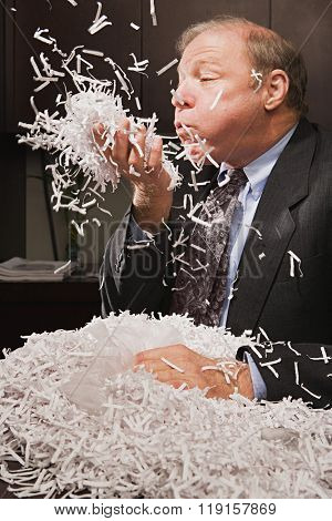 Mature businessman playing with paper shreddings