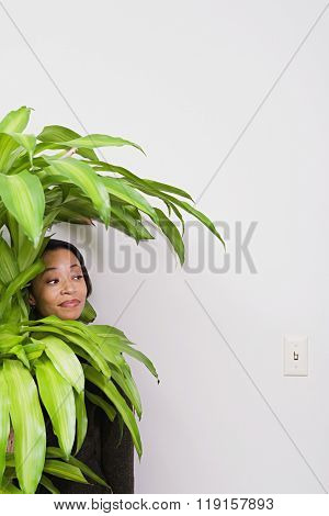 Businesswoman hiding behind office plant