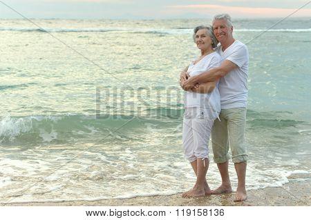 Old couple running on sea beach