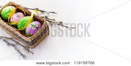 Easter background with painted eggs and pussy willow.