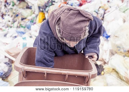 Homeless Rummages In The Dustbin Of Landfill