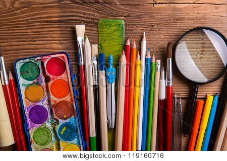 Various school and art supplies, wooden table, flat lay