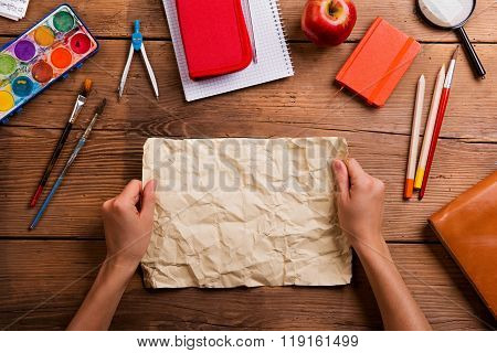 Hands of man with rumpled paper. Various school supplies.
