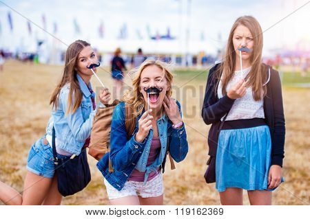 Teenage girls at summer festival with fake mustache