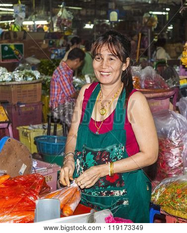 Unidentified Woman Sells Carrots And Packs Them In Plastic Bags