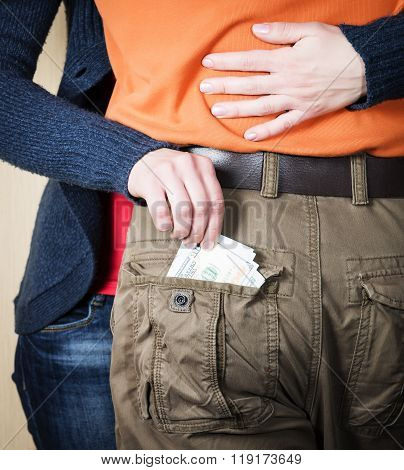 Close Up Of Woman's Hands Embracing Man And Stealing Taking Out Money Out Of His Pocket. Woman Steal
