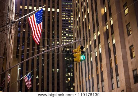 New York city traffic lights and American flags with skyscrapers on background
