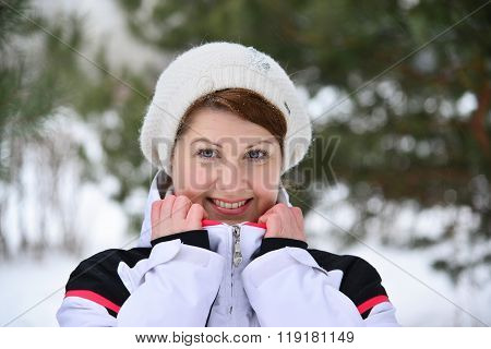 Woman In Sports Jacket And Hat At  Winter Pine Forest
