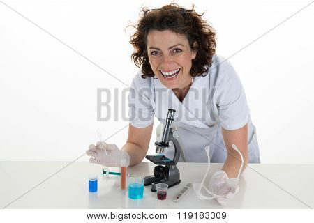 Researcher Looking At The Camera In Front Of  Microscope