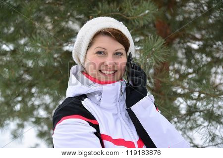 Sport Woman Talking On Phone In  Pine Winter Forest