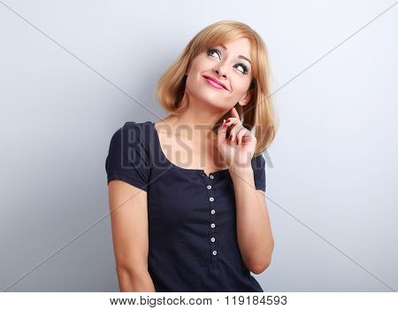 Beautiful Funny Thinking Grimacing Young Woman Looking Up On Blue Background