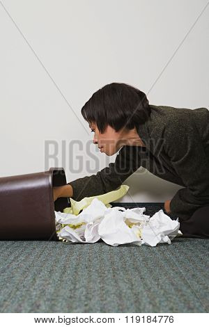 Businesswoman searching through rubbish bin