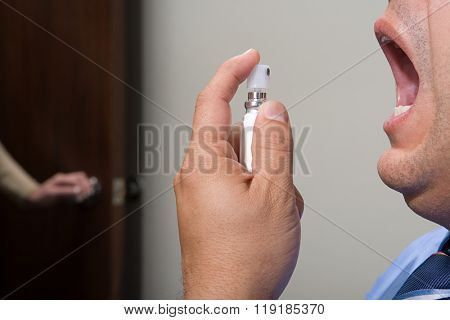 Man using breath freshener