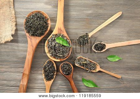 Dry tea with green leaves in wooden spoons on table background