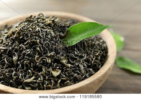 Dry tea with green leaves in bowl on wooden table background